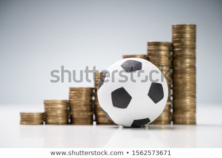 Soccer Ball In Front Of Coin Stacks On White Desk Stock photo © AndreyPopov
