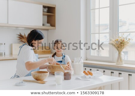 Brunette woman with smile shows little daughter how to cook, gives culinary lesson, bought different Stock photo © vkstudio