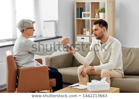 senior psychologist giving water to man patient Stock photo © dolgachov