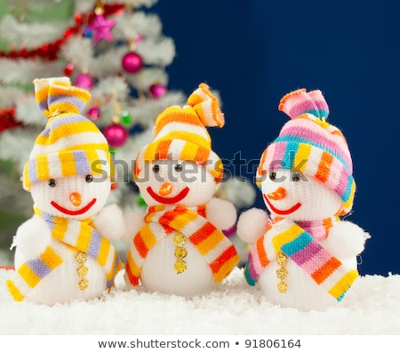 Three snowmen in front of the decorated white evergreen tree ove Stock photo © AndreyKr