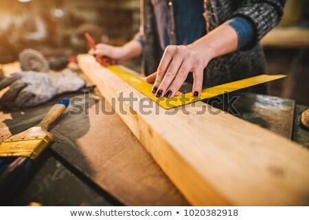Сток-фото: Female Carpenter Marking Wood With Pencil