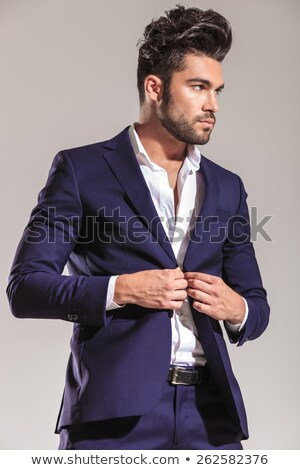 business man smiling while closing his jacket. Stock photo © feedough