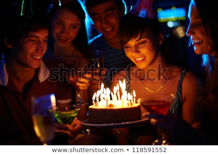 girl looking at birthday cake surrounded by friends stock photo © hasloo