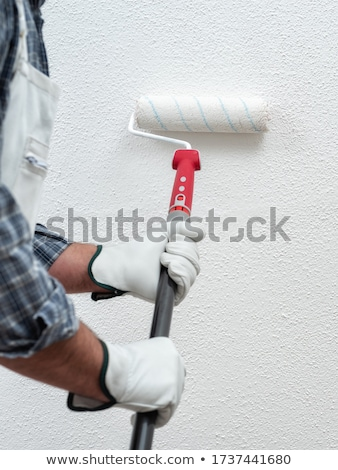 man using paint roller on wall stock photo © andreypopov