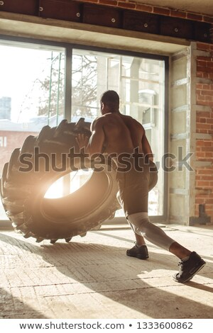 Rear View Of A Man Pushing Tire Stock photo © AndreyPopov