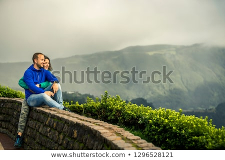 Happy young couple in love sitting on a mountain, hugging and lo Stock photo © Yatsenko