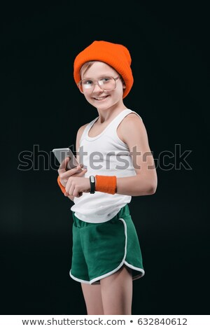 Smiling boy in eyeglasses and sportswear using smartphone isolated on black Stock photo © LightFieldStudios