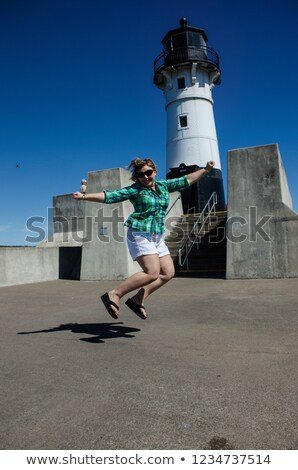 woman jumping in front of lighthouse Stock photo © IS2