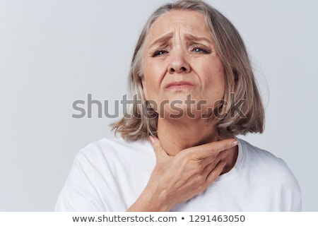 Woman with a sore throat holding her neck, On gray Background, L Stock photo © eddows_arunothai