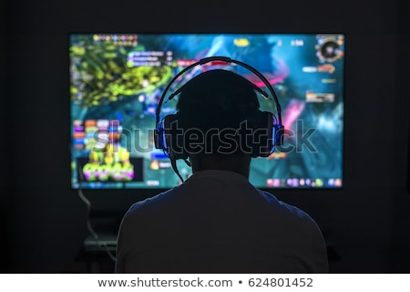 Portrait of young gamer man playing video games on computer, wea stock photo © deandrobot