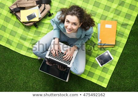 Smiling young teenage girl sitting on a blanket at a park Stock photo © deandrobot