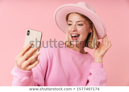 Portrait of cheerful woman taking selfie on smartphone, while ri Stock photo © deandrobot