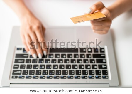 Hand of online shopper holding plastic card over keypad while paying for order Stock photo © pressmaster
