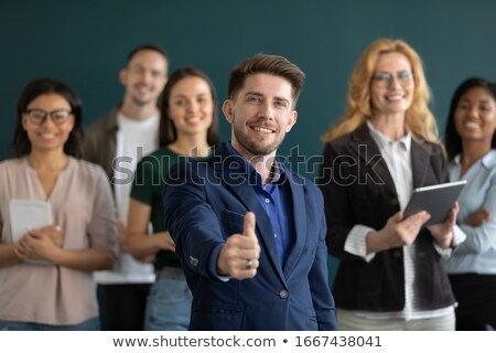 Overjoyed businessman giving thumbs up. Stock photo © lichtmeister