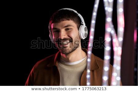 Uomo cuffie neon luci night club musica Foto d'archivio © dolgachov