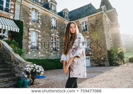 Sideways portrait of fashionable attractive young female with long hair, looks down with thoughtful  Stock photo © vkstudio