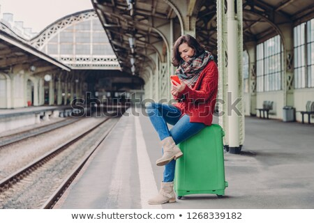 Pleased young woman has positive look, sits crossed legs at bag, holds cell phone, searches place on Stock photo © vkstudio