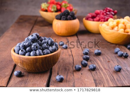 Stock photo: blueberries in a bowl with other berries in background