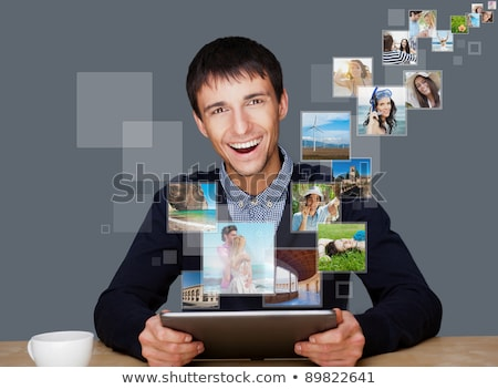 Portrait of young happy man sharing his photo and video files in stock photo © HASLOO