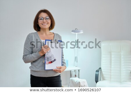 beautiful woman holding clipboard stock photo © jaykayl
