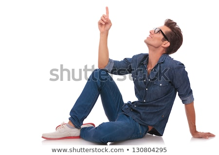 young man sitting and pointing upwards stock photo © feedough
