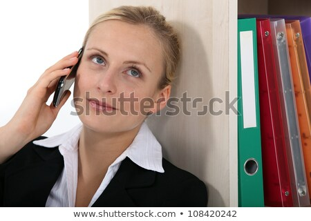Businesswoman leaning against bookcase during call Stock photo © photography33