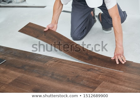 Stock photo: craftsman covering tiled floor