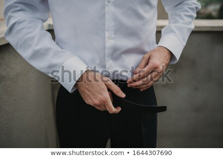 man in suit and shirt holding his belt stock photo © feedough