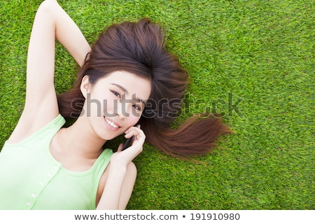 Happy Asian Woman Lying Down on Grassland Stock photo © smithore