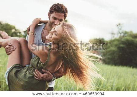 Smiling young man carrying woman Stock photo © wavebreak_media