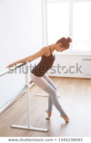 attractive young dancer practicing at the bar stock photo © dash