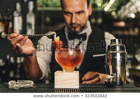 Bartender is making cocktail at bar counter at night club, toned Stock photo © Yatsenko