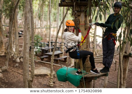Happy woman leaning on zip line while man standing on wooden platform holding rope Stock photo © wavebreak_media