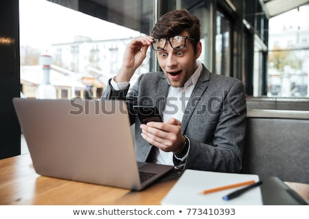 surprised business man in eyeglasses sitting by table in cafe stock photo © deandrobot