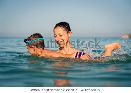 Mother teaching child to swim Stock photo © IS2