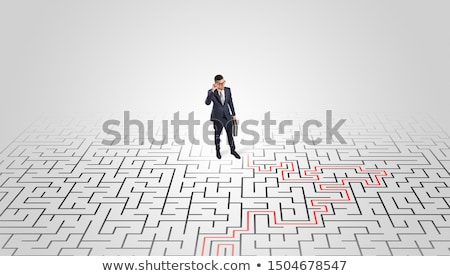 Stock photo: Young entrepreneur standing in a middle of a labyrinth