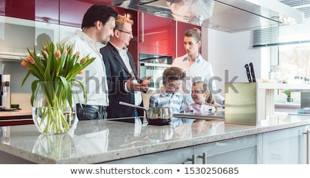 expert explaining new kitchen to family looking for one stock photo © kzenon