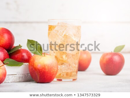 bottle of homemade organic apple cider with fresh apples in box on wooden background with sun light stock photo © denismart
