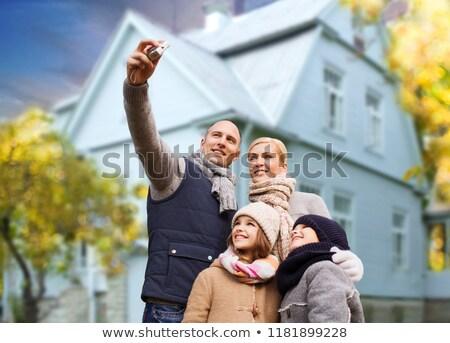 family takes autumn selfie by camera over house stock photo © dolgachov