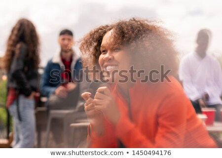 Stock photo: Happy mixed-race girl with puck watching hockey match broadcast