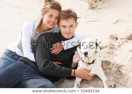 Portrait Of Romantic Teenage Couple On Beach With Dog