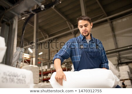 Young male worker of large polymer production factory loading sacks Stock photo © pressmaster