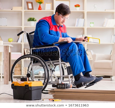 Disabled man laying floor laminate in office Stock photo © Elnur