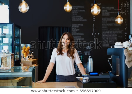 Happy young owner of restaurant or cafe standing by counter in front of camera Stock photo © pressmaster