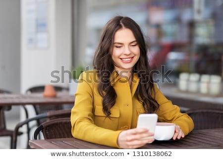 Genç kız içme sıcak çikolata şehir kafe içecekler Stok fotoğraf © dolgachov