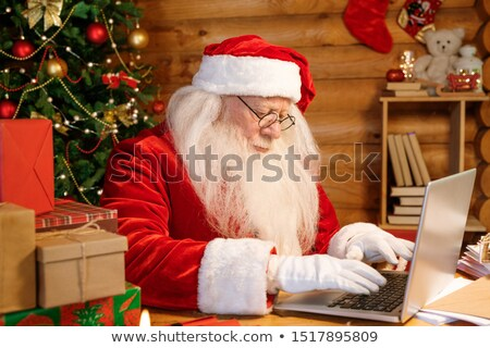 Serious Santa concentrating on answering electronic letters by laptop Stock photo © pressmaster