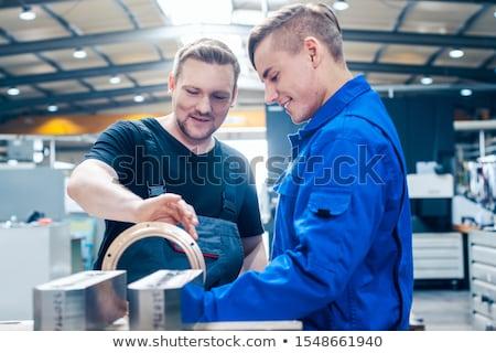 Master discussing a workpiece with his apprentice or trainee Stock photo © Kzenon