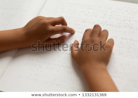 Close-up of blind mixed-race schoolboy hand reading a braille book in classroom at elementary school Stock photo © wavebreak_media