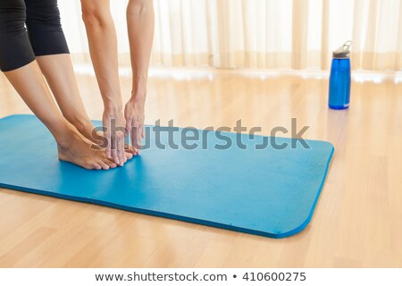 Young Woman In Sportswear Touching Toes On Mat Stock photo © HighwayStarz