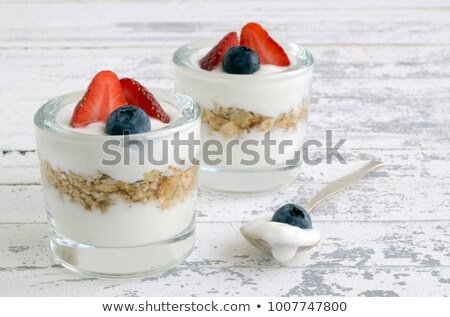 Stock photo: spoon with yogurt blueberry and a raspberry